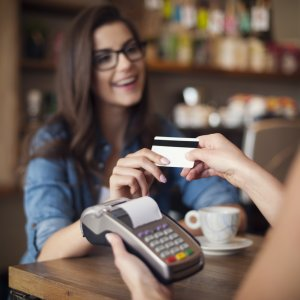 Happy woman paying for cafe by credit card, AZ TPT, sales tax, transaction privilege tax